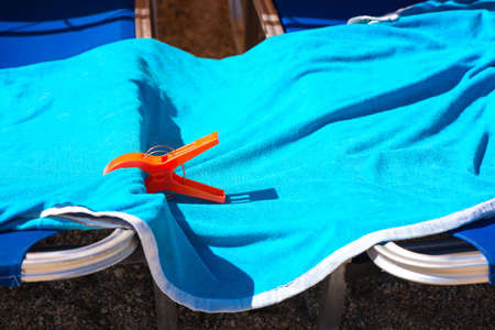 Clothespin holding a blue towel on two beach chairs Stock Photo
