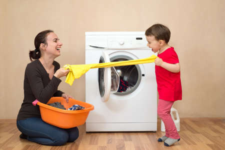 Mother and daugher playing near the washing machine