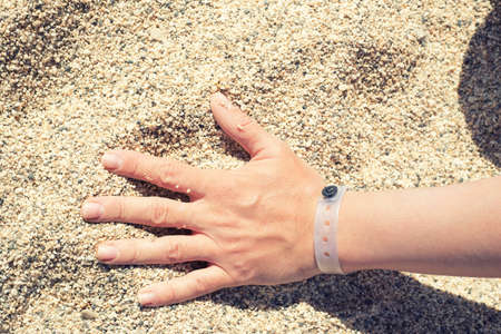 Female hand with resort bracelet on the sand Stock Photo