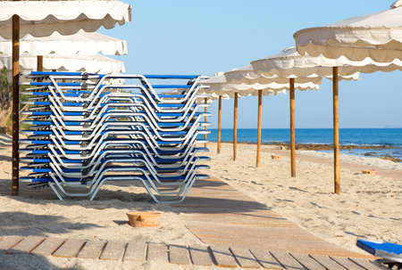 Sunbeds folded and umbrellas on the beach