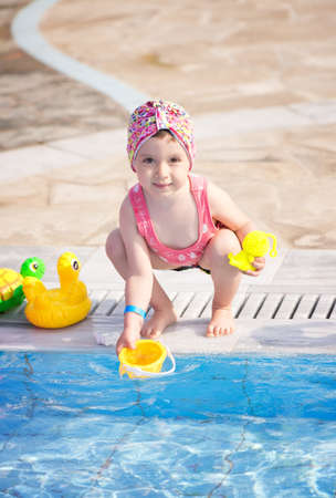 Little girl playing with toys at the pool