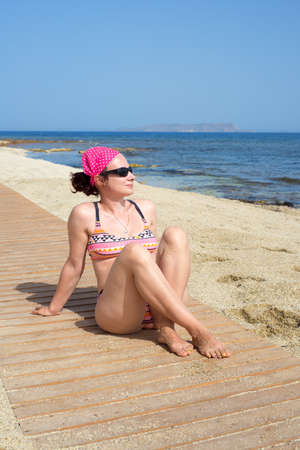 Young woman relaxing on the beach on a sunny day