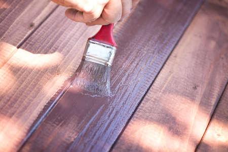 Human hand holding a brush and painting wood Фото со стока