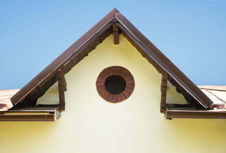Detail of a rustic building with a round window Фото со стока