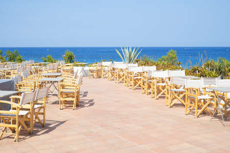Empty terrace with wooden chairs with sea view outdoors in Greece