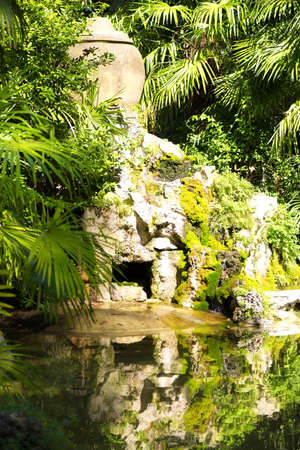 Small cave and waterfall hidden behind luxurious vegetation