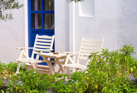 Two chairs and a table near a white wall outdoors in Greece