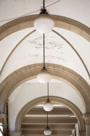 Detail of a vintage ceiling with four hanging lamps from a corridor in Rome, Italy Фото со стока
