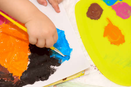 Childs hand holding a paintbrush and painting