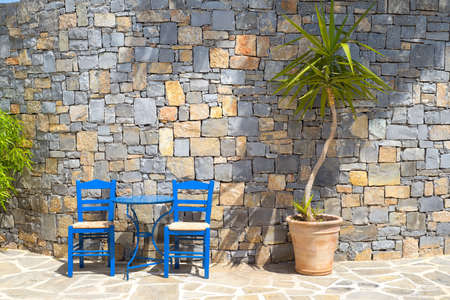 Two traditional wooden chairs and a metal table near a stone wall outdoors in Greek island Crete Фото со стока