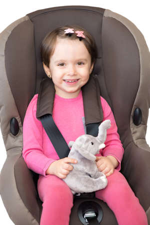 Little girl in safety car seat isolated