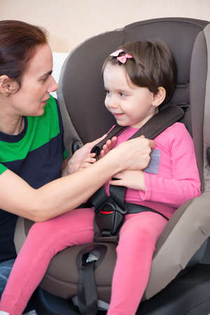 Mother securing daughter in the car seat, isolated with clipping path