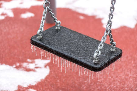 Frozen swing with icicles outdoors after a freezing rain phenomenon
