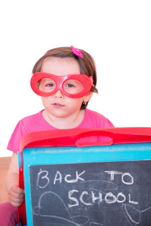 Little girl with plastic toy eyeglasses holding a blackboard