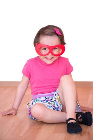 Little girl with toy eyeglasses and dance shoes sitting Stock fotó