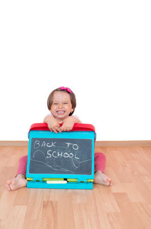 Little girl holding a blackboard with the text Back to school written on it