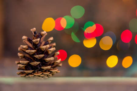 Closeup of a fir tree cone with lights in background, Christmas symbol