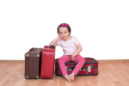Little girl sitting on vintage suitcase