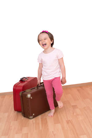 Little girl with luggage ready to leave