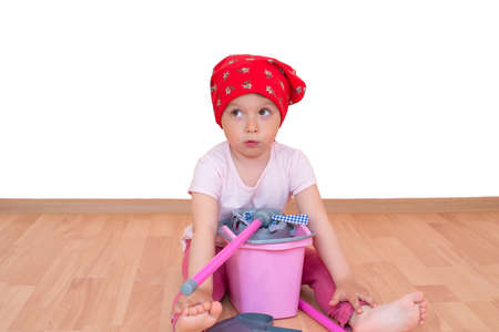 Barefoot little girl with mop and bucket sitting on the floor