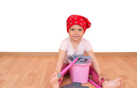 Barefoot little girl with toy cleaning equipment sitting on the floor