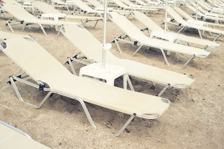 Sun beds on the sand in a row, vintage photography