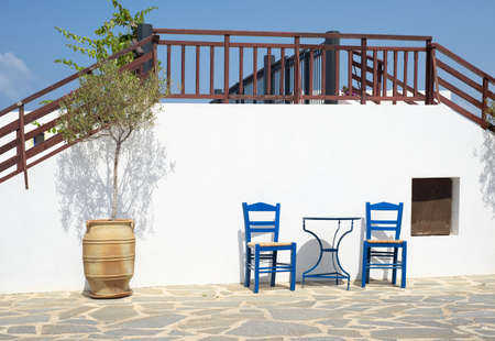 Two traditional wooden chairs and a metal table outdoors in Greek island Crete