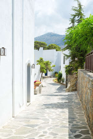 Narrow passage with white buildings and trees from Greece Stock fotó