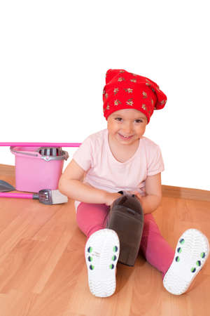 Little girl with toy cleaning equipment sitting on the floor