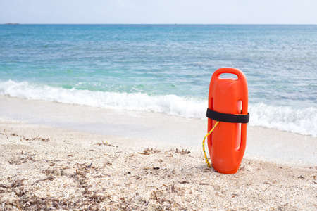 Orange buoy standing on the sand in front of the sea, safety concept