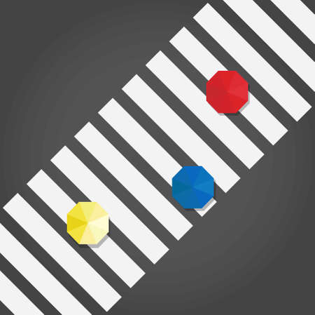 Top view of a three umbrelas: yellow, blue and red on a pedestrian crosswalk