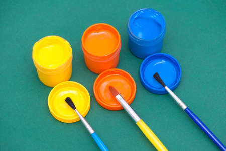 Three paintbrushes and gouaches of different colors: yellow, orange, blue Stock fotó - 131606012
