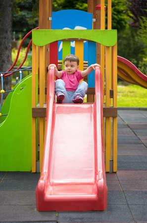 Petite fille sur la diapositive dans une aire de jeux