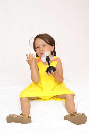 Little girl holding a plastic toy fan Stock fotó