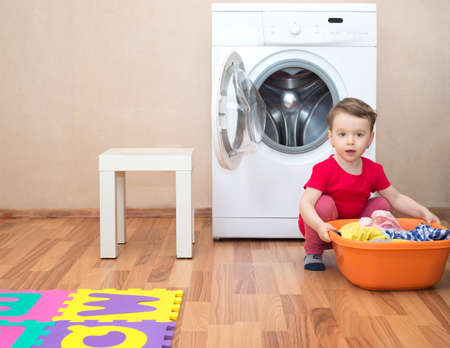 Little girl with a washbowl full of clothes in front of the washing machine