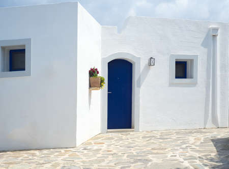 Detail of a typical greek building with white walls and blue door Stock fotó