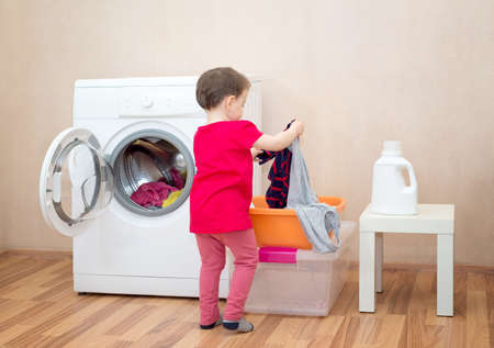 Little girl holding clothes near a washing machine Stock fotó - 135010858