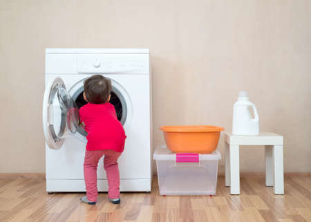 Little girl with her hands inside a washing machine Stock fotó