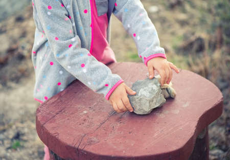 Child playing with stones on a wooden table Stock fotó - 135011051