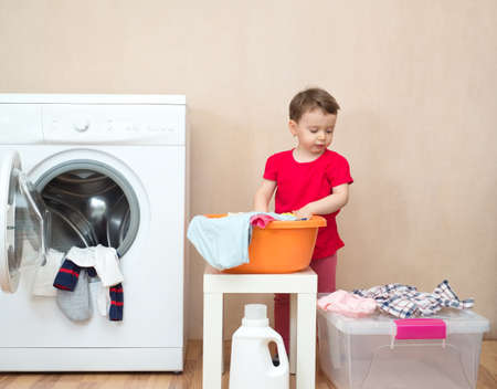 Little girl doing the laundry near a washing machine Stock fotó