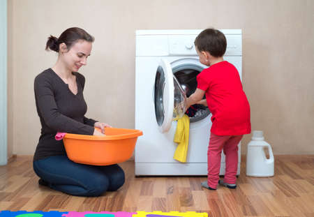 Mother and daughter near the washing machine