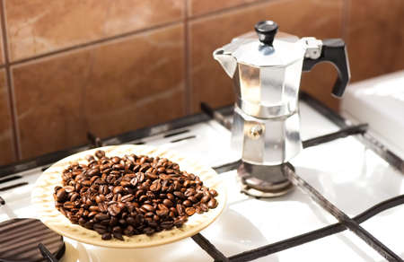 Coffee beans on a plate and moka coffe pot on a gas stove