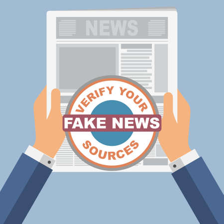 Hands of a man holding a newspaper with the text fake news on it