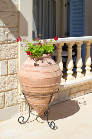 A large decorative pot with geranium flowers