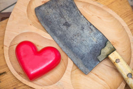 Meat cleaver and heart on a wooden board Stockfoto