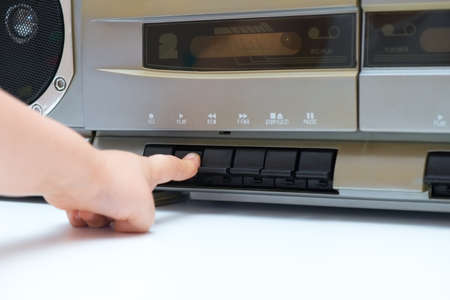 Child pushing the play button of an old cassette player