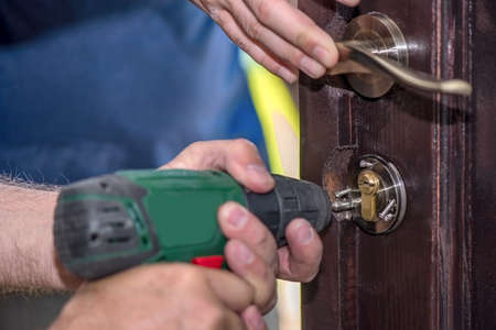 Men repairing a door using a drill