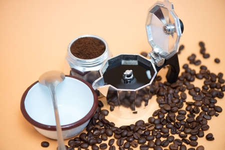 Coffee in a moka pot with coffee beans, ground coffee and an empty cup with a spoon on it