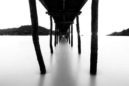 Black and white wooden bridge extending into the sea