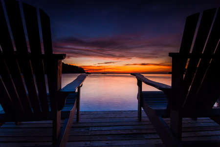 Beach chairs on a wooden bridge with sunset